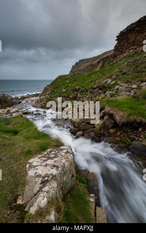 A stream or waterfall tumbling or running through the hillside down to the beach in the cot valley at porth nanven in west cornwall neat st just. - Stock Photo