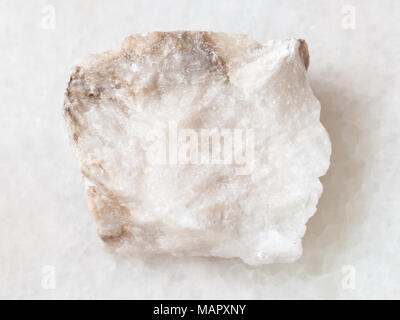macro shooting of natural mineral rock specimen - raw Anhydrite stone on white marble background - Stock Photo