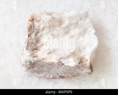 macro shooting of natural mineral rock specimen - rough Anhydrite stone on white marble background - Stock Photo