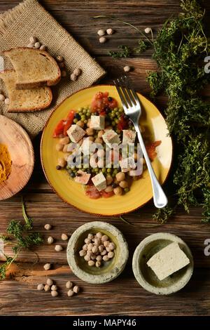 tofu salad, chickpeas, peas and tomato - vegetarian food - closeup - Stock Photo