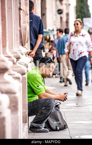 A Mexican man sitting on the stoop of his house, checking something out on his cell phone; Aguascalientes, Mexico. - Stock Photo