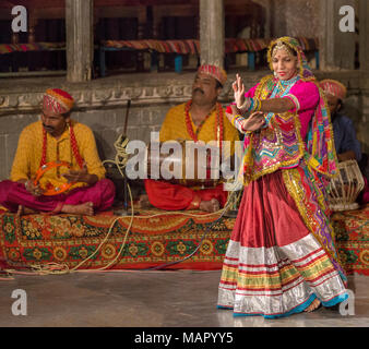 An Indian woman wearing a multi-coloured costume performs a Rajasthani folk dance, with musicians playing acoustic instruments, Udaipur, Rajasthan, In - Stock Photo