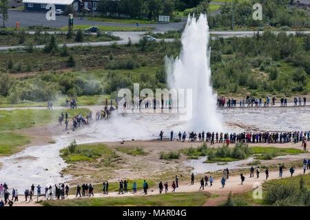 Tourists watch the eruption of the Strokkur geyser, Haukadalur valley, Hvita River, Iceland, Polar Regions - Stock Photo