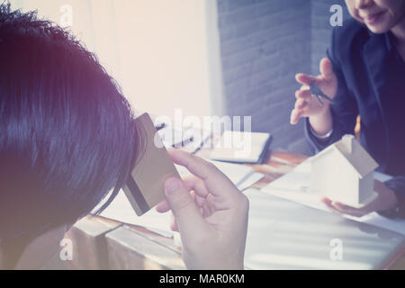 balancing the property sector in business, hands and a wooden house - Stock Photo
