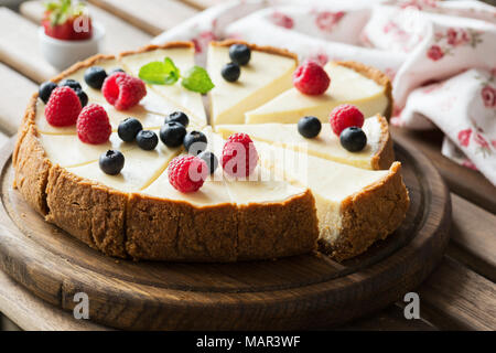 Classical Cheesecake with fresh berries on wooden board, selective focus, horizontal composition - Stock Photo
