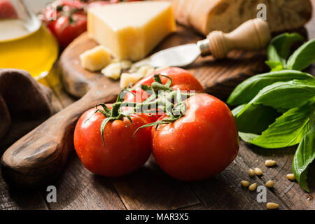 Tomatoes on vine, olive oil and parmesan cheese. Italian food background or still life - Stock Photo