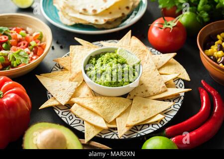 Guacamole, tortilla chips and salsa. Mexican food selection. Closeup view, selective focus - Stock Photo