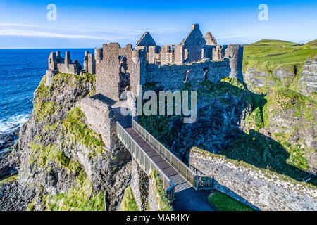Ruins of medieval Dunluce Castle on a steep cliff. Northern coast of County Antrim, Northern Ireland, UK. Aerial view at sunset light. - Stock Photo