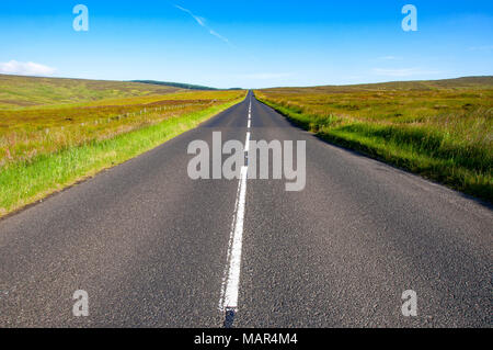 Straight asphalt road with a white line to the horizon between the fields and grass. County Antrim, Northern Ireland, UK - Stock Photo