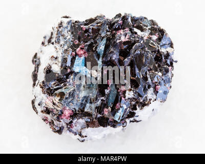 macro shooting of natural mineral rock specimen - rough Gneiss stone with biotite, kyanite, tourmaline crystals on white marble background from Hit-is - Stock Photo