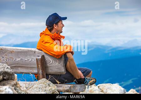 Wanderer auf der Bank bei Gipfelrast - Stock Photo