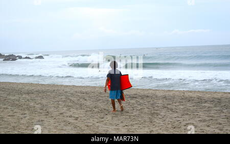 Mexican boy walking on sandy beach carrying a red surf board and flippers - Stock Photo