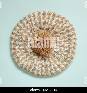 Knitted hat with pompom isolated on light green background - Stock Photo