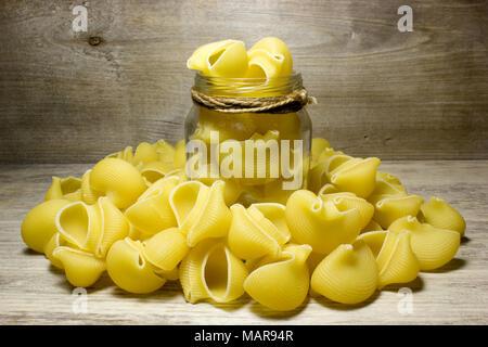 Noodles seashells on wooden background - Stock Photo