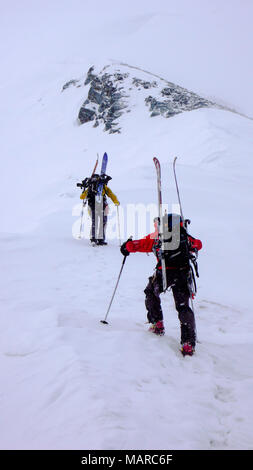 two male mountain climbers on a backcountry ski mountaineering tour in bad weather - Stock Photo