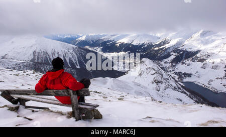 backcountry skier takes a break and sit on a summit bench and enjoys the view of Davos in winter - Stock Photo