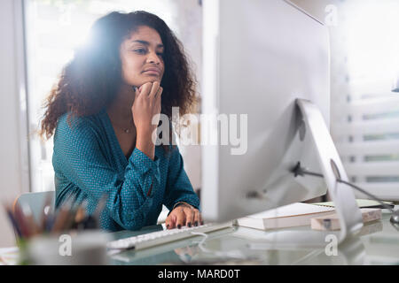 Beautiful young black woman sitting at her desk in front - Stock Photo