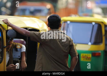 Bangalore, India - October 16, 2016: Two local rickshaw drivers spotted waiting for passengers at a rickshaw stand in Residency Road, Bangalore. - Stock Photo