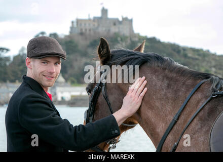 Handsome Male Horse Rider standing walking his horse, wearing flat cap, white trousers and black boots on beach in front of St Michael's Mount - Stock Photo