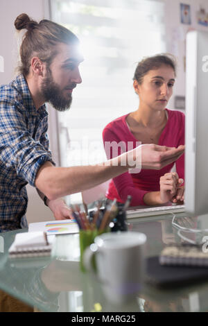 Two colleagues, man and woman sharing ideas about a project - Stock Photo