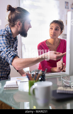 Two students, one man and one woman sharing ideas about project - Stock Photo