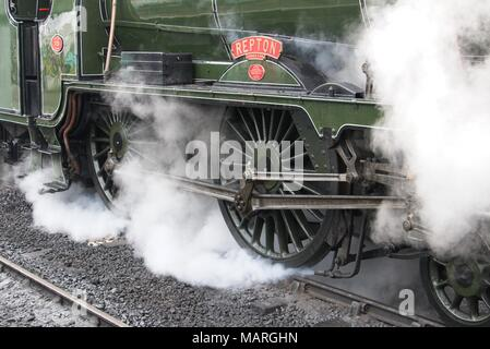 A closeup view of the drive wheels of Repton, a schools class steam engine 926 with steam surrounding the wheels. - Stock Photo
