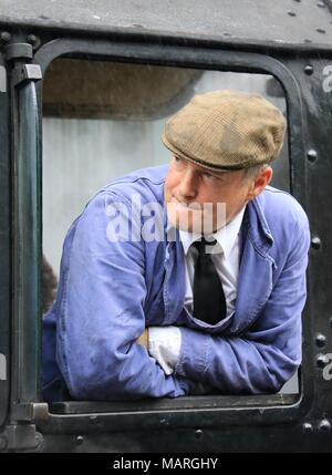 A portrait of a steam engine driver in blue overalls leaning out of the cab window of a black steam train. - Stock Photo