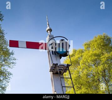 A closeup view of a vintage railway signal in the stop position, against a blue sky. - Stock Photo