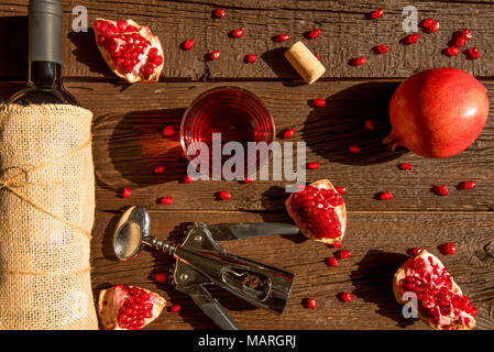 Top view pomegranate wine, bottle opener and fruit - Stock Photo