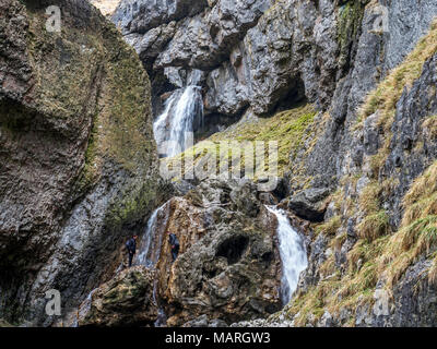 Waterfalls and walkers on the steep path at Gordale Scar near Malham Yorkshire Dales England - Stock Photo