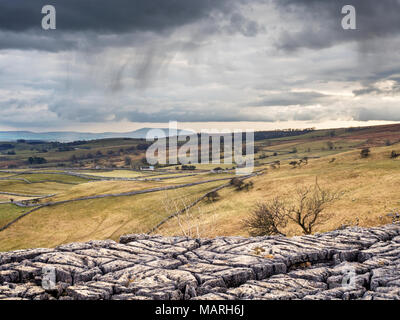 Rain falling over Malhamdale from Malham Cove with Pendle Hill on the Horizon Malham Yorkshire Dales England - Stock Photo