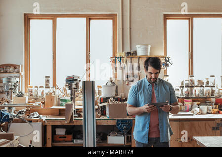 Young carpenter using a digital tablet in his workshop - Stock Photo