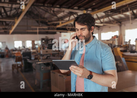 Woodworker using a phone and tablet in his large workshop - Stock Photo
