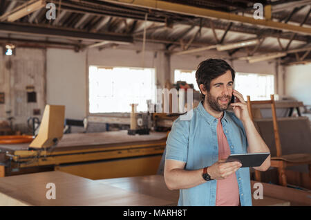Woodworker using a cellphone and tablet in his workshop - Stock Photo