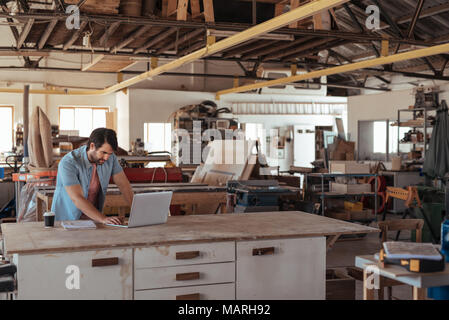 Young woodworker working online at a bench in his workshop - Stock Photo