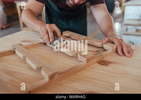 Artisan skillfully sanding a piece of wood in his workshop - Stock Photo