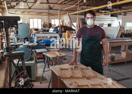 Young woodworker in protective workwear standing in his studio - Stock Photo
