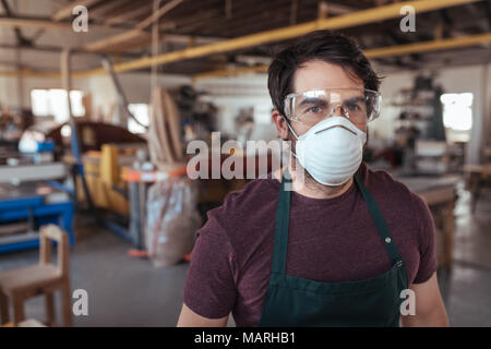 Young woodworker standing alone in his workshop wearing protective gear - Stock Photo