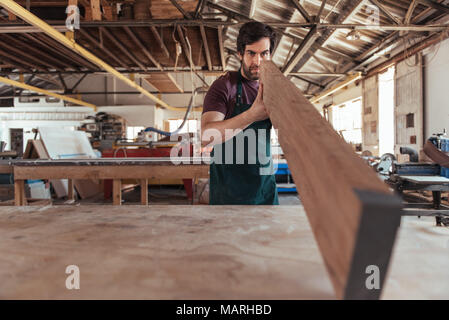 Woodworker skillfully inspecting a wooden plank in his workshop - Stock Photo