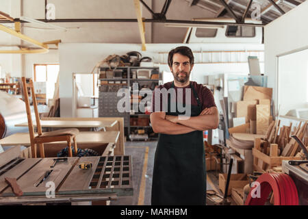Craftsman standing by a bench saw in his woodworking shop - Stock Photo
