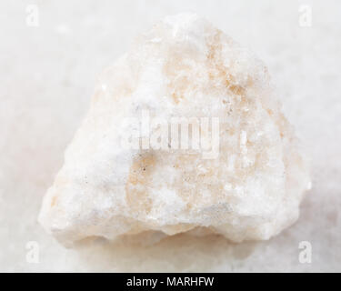 macro shooting of natural mineral rock specimen - rough anhydrite stone on white marble background from Adygea, Russia - Stock Photo
