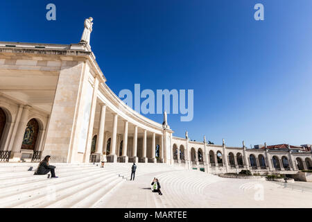 Fatima, Portugal. Tourists at the famous colonnade of the Shrine and Sanctuary of Our Lady of Fatima, with a Via Crucis or Way of Sorrows - Stock Photo