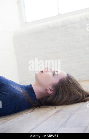 Beautiful woman laying down on the floor looking up - Stock Photo