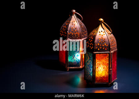 Two colorful oriental Lamp lanterns burn with candles with color reflection on dark black background for Ramadan and other islamic muslim holidays, sp - Stock Photo