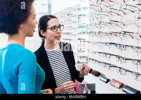 Black woman inspecting glasses in optician shelf - Stock Photo