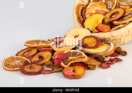 Close Up Of Organic Raw Sun Dried Fruits Pouring From Basket Mix Of Oranges, Plum, Strawberries, Golden Berries And Peach Isolated on white Background - Stock Photo