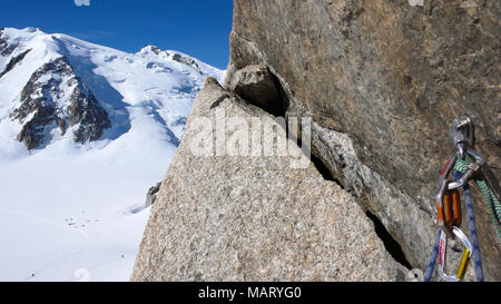 bolt and quick draw with climbing equipment on an exposed and steep climbing route in the French Alps with Mont Blanc in the background - Stock Photo