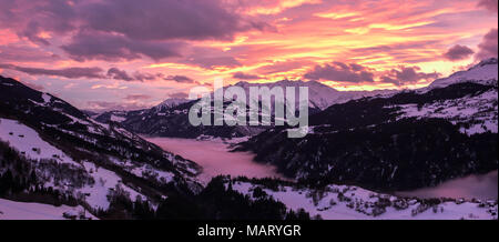 majestic and colorful sunset over a winter mountain landscape in the Alps - Stock Photo