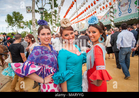Young women dressed in colourful flamenco dresses at the Seville April Fair, Spain - Stock Photo