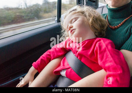Sleeping two year old child riding in back seat of car on mother's lap using seat belt, UK - Stock Photo